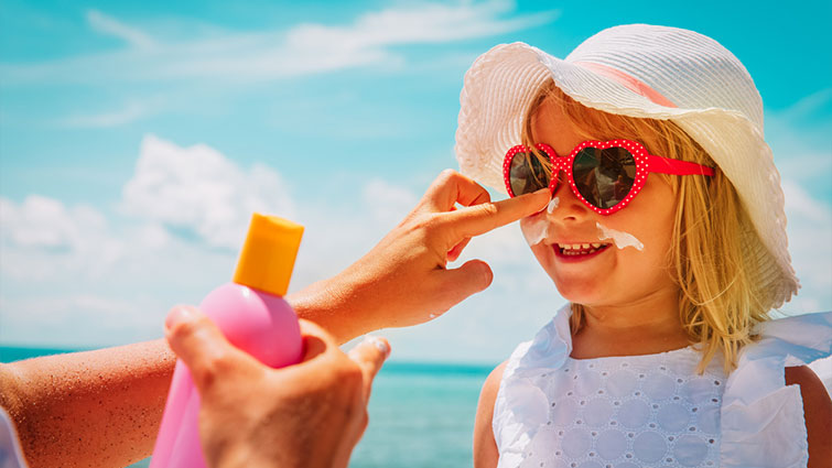 Parent putting sunscreen on child wearing sunglasses