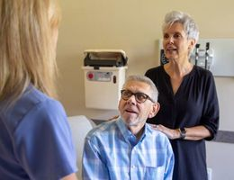 Patient David Campbell sits with his wife Pam Campbell while talking to a nurse.