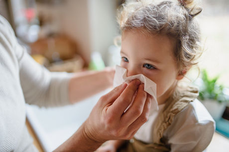 Unrecognizable father with small sick toddler daughter indoors at home, blowing nose.