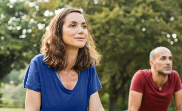 Woman in blue shirt outdoors with man in red shirt doing yoga