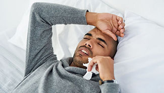 Man sick in bed holding tissue