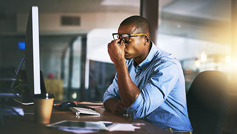 man at desk at work looking stressed