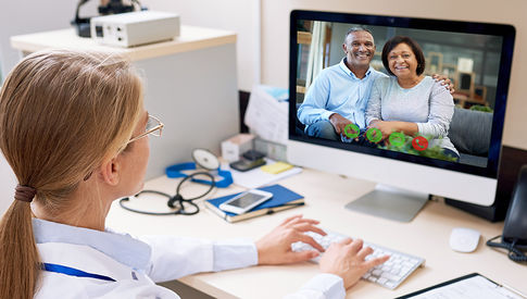 doctor looking at monitor with video visit couple on screen