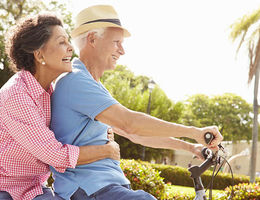 Older couple riding a bike to stay healthy
