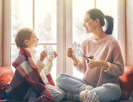 female child and female adult cut snowflakes in front of snowy window