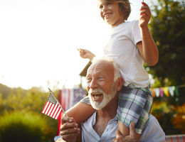 Boy on grandfathers shoulders holding American flag.