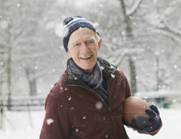 man holding a football in the snow