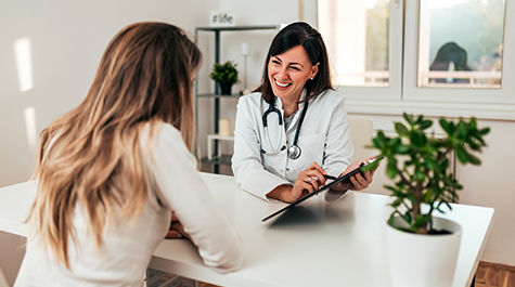 happy female doctor talking to female patient in an office looking at a clipboard
