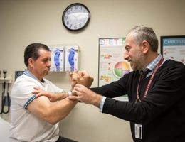 Doctor testing strength on patient
