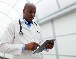 Doctor using tablet in medical walkway