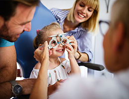 ophthalmologists putting glasses on a child