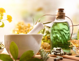 photo of oil bottles, herbs, and a white mixing bowl