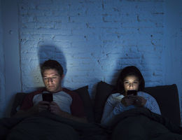 couple looking at there tablets before bed